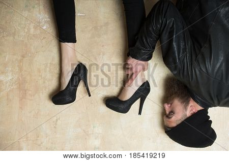 Funny female legs in elegant fashion stylish black shoes on high heels over head of bearded man or hipster with long beard in black hat and leather jacket on beige plastered wall. Upside down
