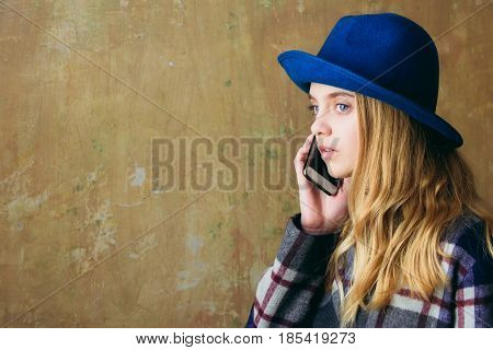 caucasian girl speak or talking on phone woman hold smartphone in green hat on beige background copy space