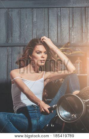 Girl Biker Sitting On Vintage Motorcycle In Garage