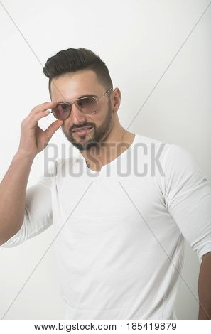 sexy macho. Sexy macho bearded handsome man young caucasian model with stylish hair haircut posing in fashionable retro aviator sunglasses on white background. Eye care and eyewear poster