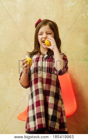 Cute Girl With Winking Eyes Eating Lemons