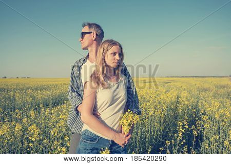 Man With A Beautiful Young Woman Are Hugging, Standing In A Field