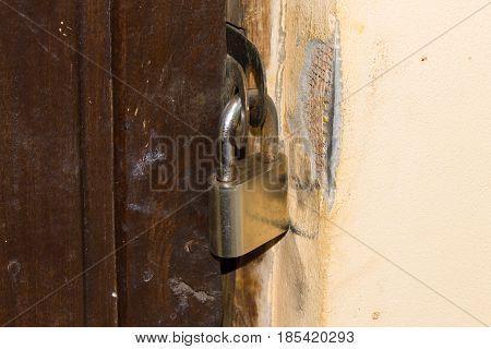 Old metal chrome padlock on the old doors