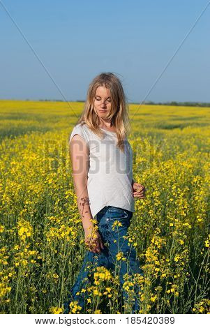 Romantic Young Woman, Blonde, With Flying Hair, Poses In A Field