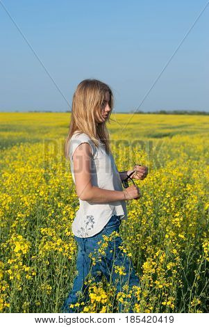 Beautiful Young Woman, Blonde Relaxes In A Field Of Yellow Flowers
