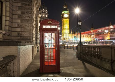 London, UK - 24 January 2017: Popular tourist Big Ben and Houses of Parliament with red phone booth in night lights illumination