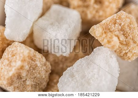 White sugar and brown sugar cane cubes. Close up with selective focus.