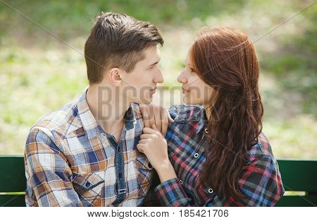 Flirting young couple sitting on a bench in the park and looking into each other's eyes