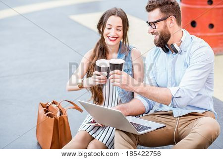 Modern businessman and businesswoman working with laptop and coffee outdoors on the heliport ground. Lifestyle business concept