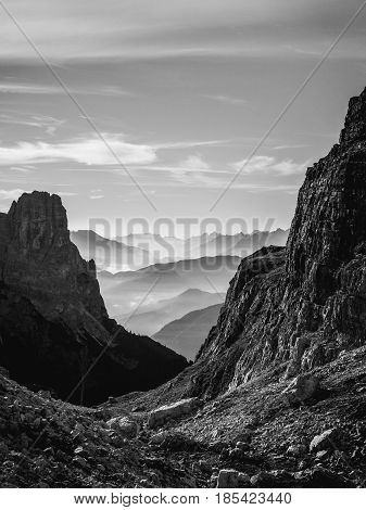 Black and white landscape view of hazy rolling mountains and hills in the Italian Dolomites at sunrise. Portrait orientation.