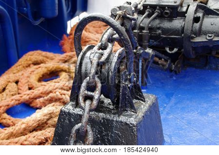 Black painted anchor winch with chain on ship