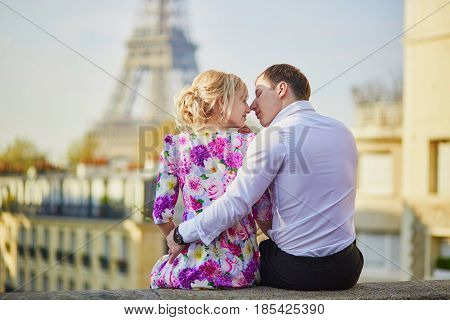 Romantic Couple Sitting On The Roof Near The Eiffel Tower In Paris, France