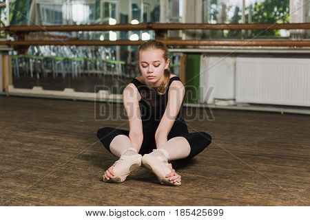 Young beautiful ballerina warming up in ballet class. Beautiful ballerina doing stretching exercises in ballet class