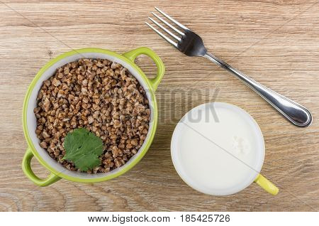 Green Bowl With Boiled Buckwheat, Cup Of Milk And Fork