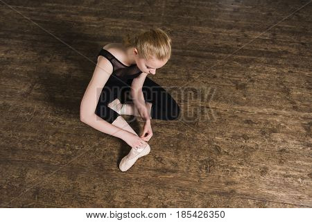 Young ballerina or dancer girl putting on her ballet shoes on the wooden floor. Female dancer ties on her pink ballet slippers with ribbons. Top view.