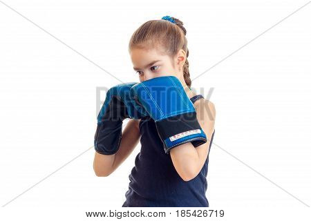 little girl with pigtail stands in the large blue boxing gloves in front of a camera isolated on white background