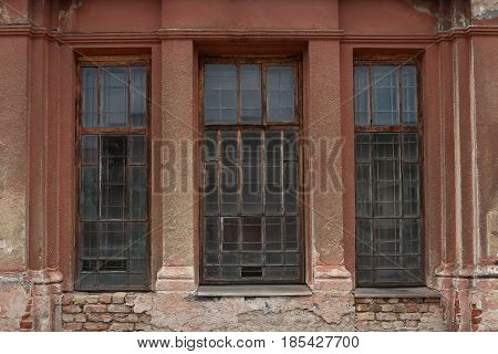 Old building facade with window. Facade of old abandoned building with three large windows.