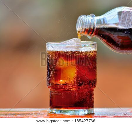 Pouring cola into a glass of ice on blur background.