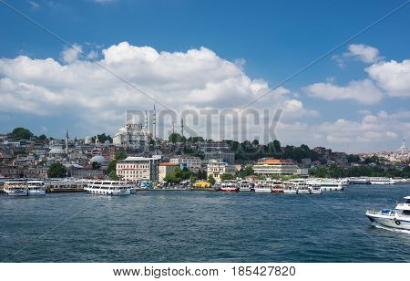 ISTANBUL TURKEY - JUNE 25 2015: View on the Suleymaniye Mosque and boats in Eminonu Istanbul Turkey