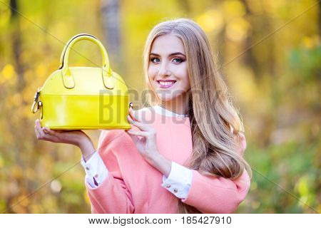 A beautiful woman portrait in romantic autumn decadence, in a beautiful orange coat holds a yellow leather bag in her hands. Advertising leather bag
