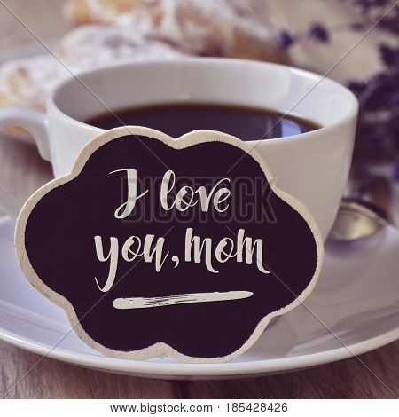 closeup of a black cloud-shaped signboard with the text I love you mom written in it, next to a cup of coffee on a table set for breakfast with some viennoiseries in a plate in the background