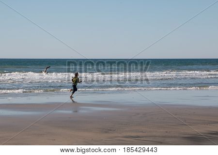 Young Girl Running on the Beach Shorline