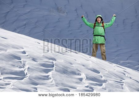Male Tourist climber with arms upraised on the background of snowy mountain landscape. Gesture of success.