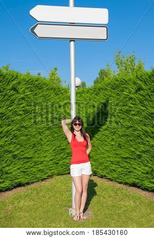 Beautiful young girl on the green background of the shrubbery near the white pointer. Standing on the green lawn of grass. The pure blue sky. Girl smiling