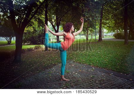 young woman practice yoga in nature in park by the tree full body shot