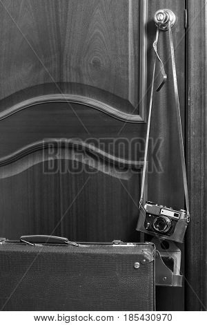 Old retro camera and travel bag near the door