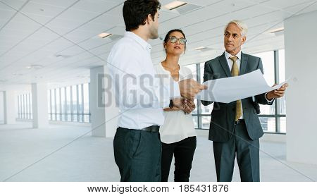 Business people and real estate agent discussing over blueprint of empty office space. Real estate agent showing new office space to potential clients.