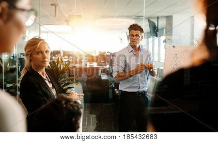 Mature businessman making a presentation on a flip-chart and discussing. Business team during strategy meeting in modern office.