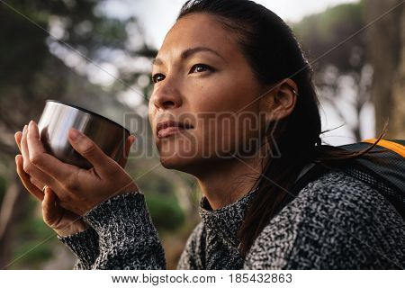 Close up side shot of female hiker resting outdoors with a coffee and looking away. Asian woman having coffee.