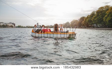 Young Friends Sitting In Pedal Boat Enjoying Summertime