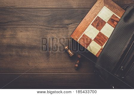 chess board with figures in the brown bag on wooden table
