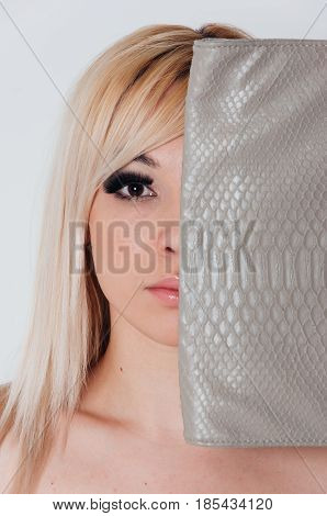 half face of fashion model with makeup. The other half is covered with a woman's bag with snake skin