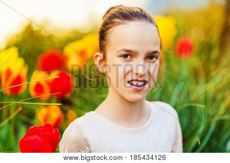 Spring portrait of sweet little girl wearing party dress, sitting outdoors with yellow and red tulips on background. Preteen girl with teeth braces