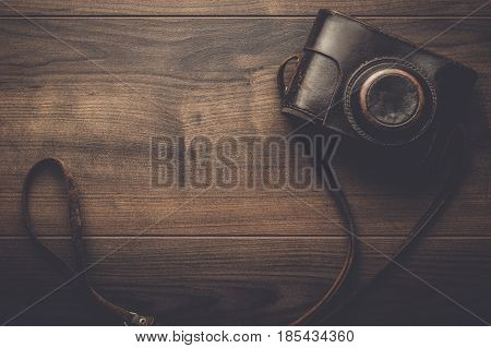 wooden background with retro still camera in camera case. brown photo retro camera case. leather camera case with strap