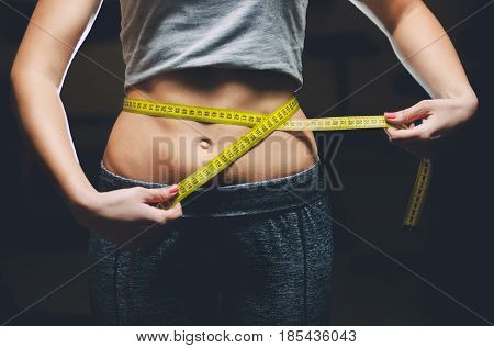 Slim Girl Bodybuilder Centimeter Measuring Her Waist In A Gym. Sports Concept, Fat Burning And A Hea