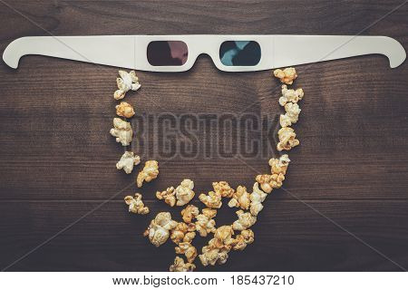 anaglyph glasses and popcorn on wooden table making bearded face