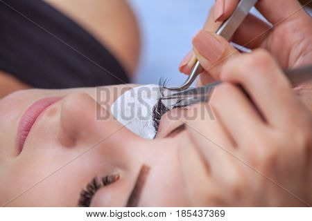 Makeup Master Corrects, And Strengthens Eyelashes Beams, Holding Out A Pair Of Tweezers In A Beauty