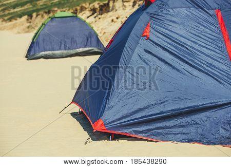 Two Blue Tents Set Tourists On The Beach, On The Sea Coast.