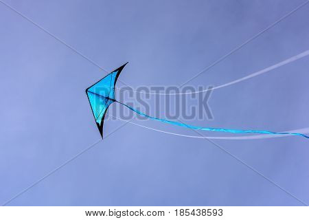 Blue kite floating in the blue sky. Kite with blue sky background.