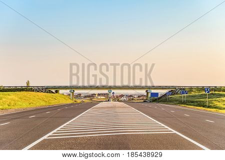 Multi-lane countryside asphalt road with marking. Intersection of the country roads on two levels. Disappearing into the distance perspective. Belgorod region Russia.