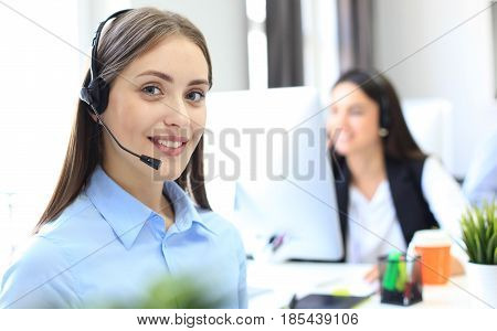 Smiling female call centre operator doing her job with a headset while looking at camera