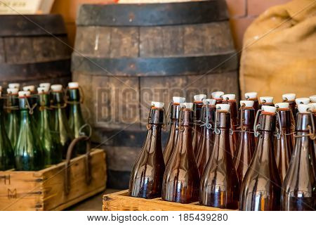 A bottle crate stacked on top of a wooden barrel at an attic of a beer brewery Old barrels and beer bottles