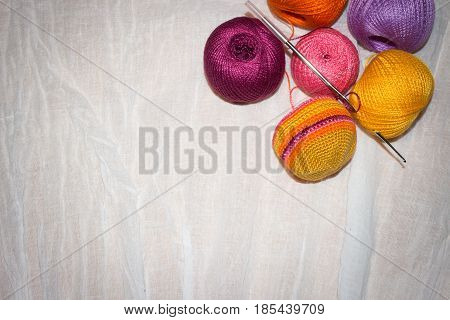 crocheting in progress and colorful cotton thread balls on the white linen background with space