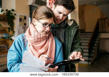 Man and woman at work, look in the folder and write. Busy and focused look