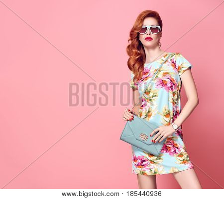 Fashion Beauty woman in Summer Outfit. Glamour Sexy Redhead Model in fashion pose. Trendy Floral Dress, Stylish wavy hairstyle, fashion Sunglasses, Luxury summer Clutch. Playful summer Girl on Pink