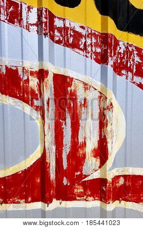 Part of a painted commercial sign on corrugated steel wall forms a colorful abstract